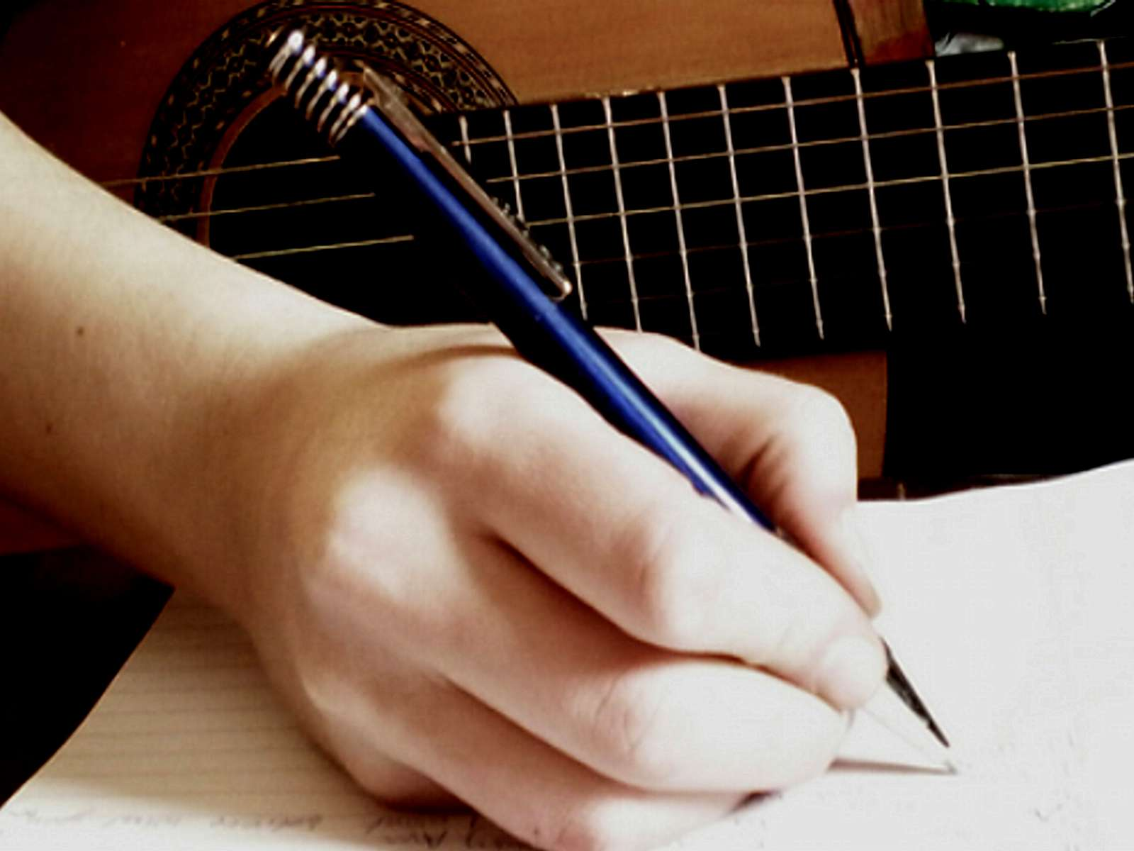 image of someone writing a song with pen, paper and guitar